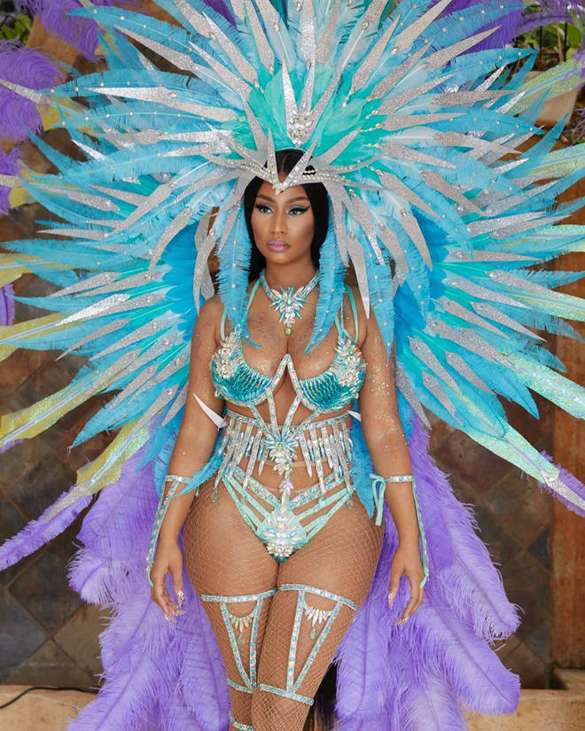 Nicki Minaj apologised for her husband's behaviour at Trinidad Carnival, during which she wore a dazzling blue and purple costume.