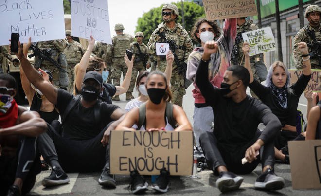 Peaceful protesters in Los Angeles as the National Guard keeps watch on Sunset Boulevard in Hollywood.