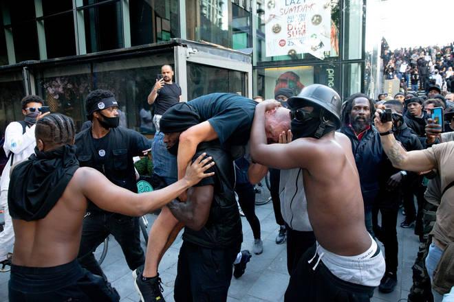 Patrick Hutchinson carries injured man amid far-right riots