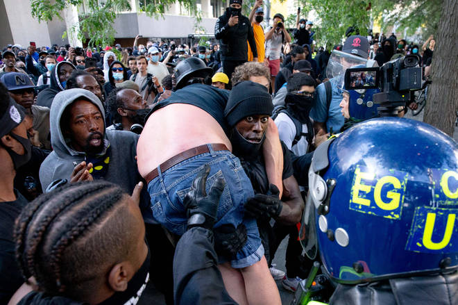 Far-Right supporter carried to safety by Black Lives Matter supporter