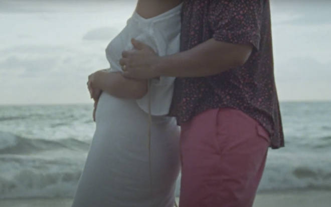 John, 41, can be seen cradling his wife's small baby bump in the 'Wild' music video.
