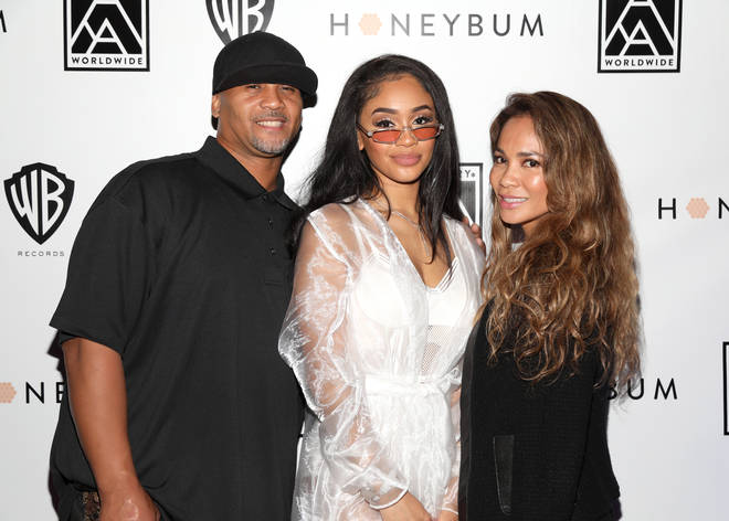 "Saweetie poses with her parents Johnny and Trinidad at her ""High Maintenance"" Listening Event in 2018."