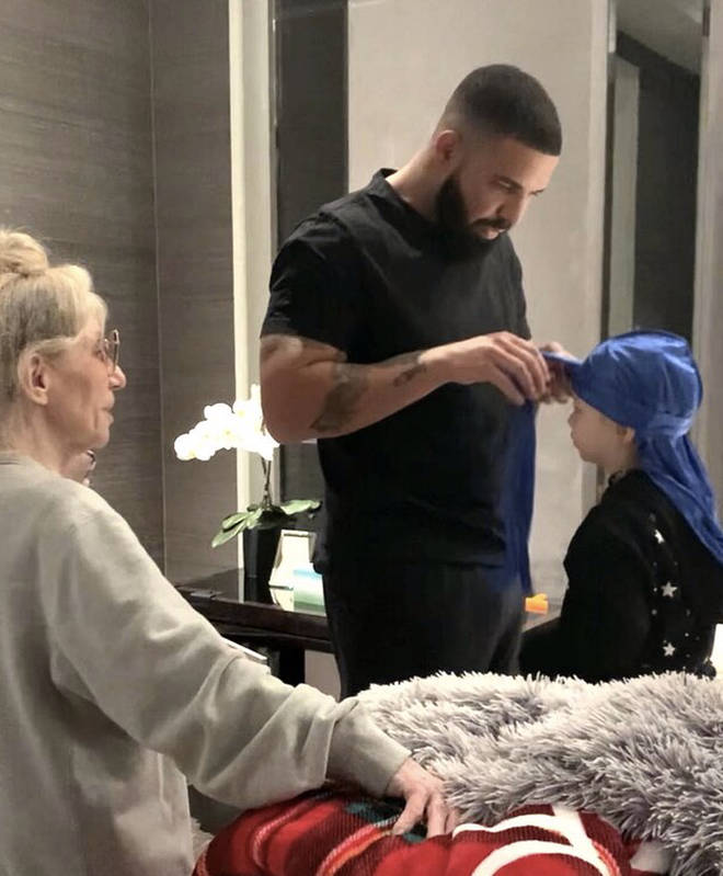 Drake shares a photo of him tying Adonis' durag, with his mother Sandi Graham in attendance.
