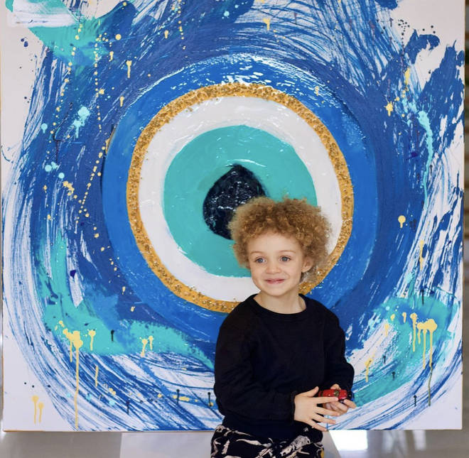 Adonis poses infant of a 'evil eye' painting made by his mother, Sophie Brussaux.