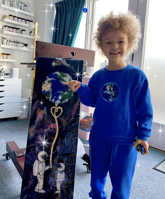 Adonis poses in-front of a painting his mother made for #EarthDay