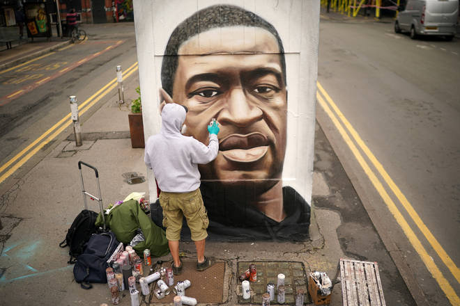 Graffiti artist Akse spray paints a mural of George Floyd in Manchester's northern quarter on June 03, 2020.