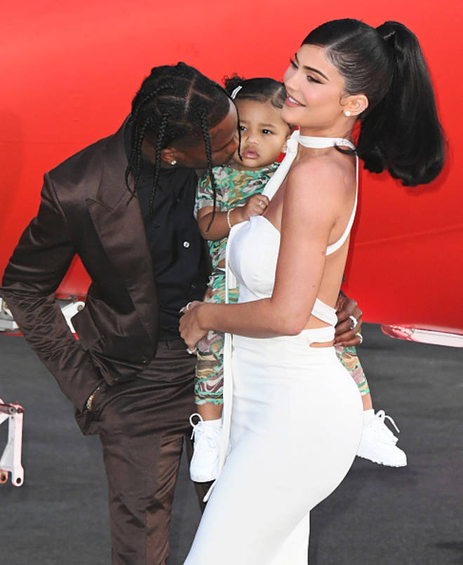 Travis posed with Kylie Jenner and baby Stormi on the brown carpet in LA