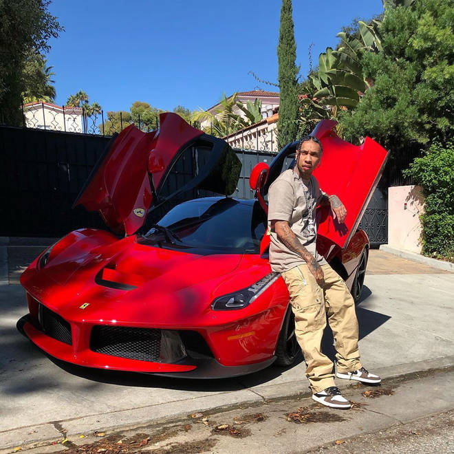 Tyga leans against his red Ferrari in the photo, spotting a pair of Travis Scott's Air Jordan 1's.